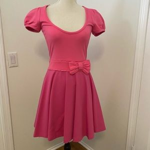Pink mini skater dress with a bow.